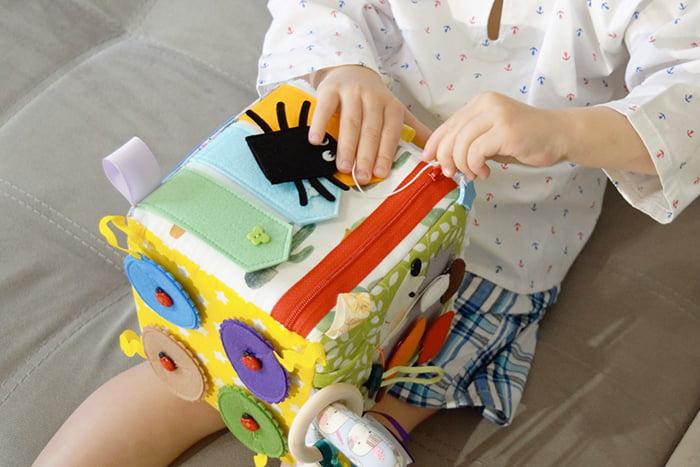 Ребенок играет с развивающим кубиком