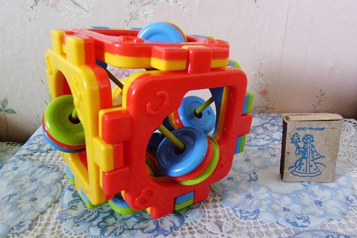 Пластмассовый развивающий кубик с погремушками внутри
