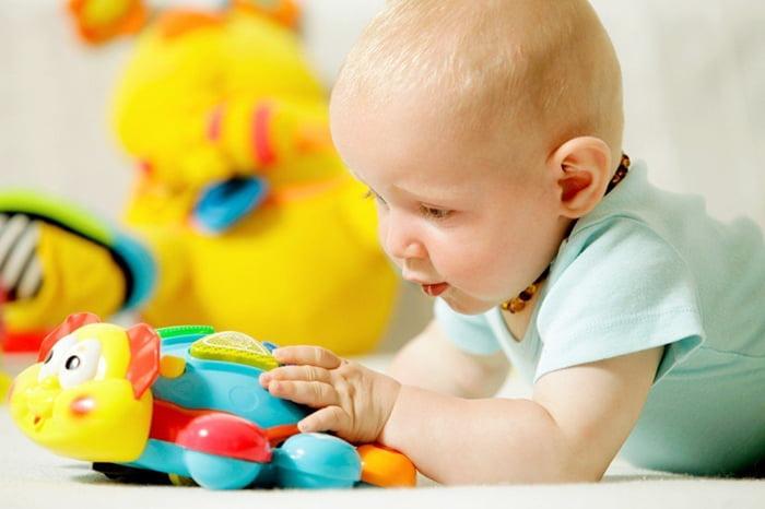Малыш ощупывает яркую игрушку