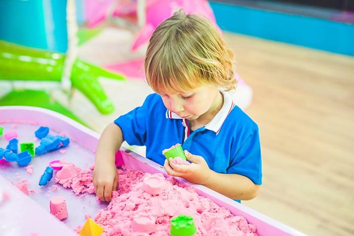 Ребенок играет с кинетическим песком