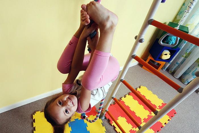 Девочка висит вверх ногами на шведской стенке дома