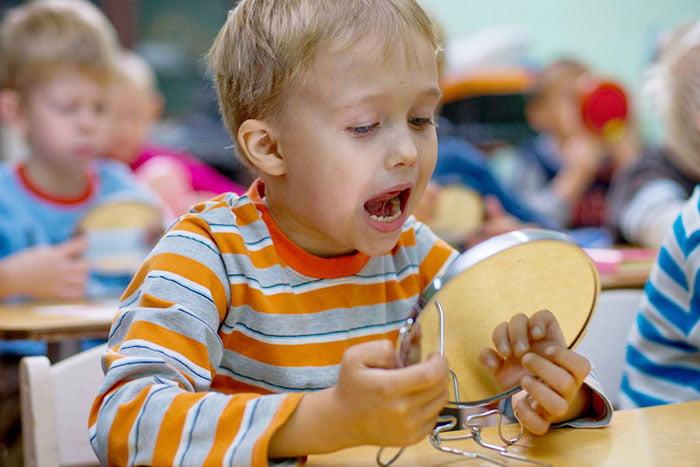 Ребенок выполняет артикуляционное упражнение перед зеркалом