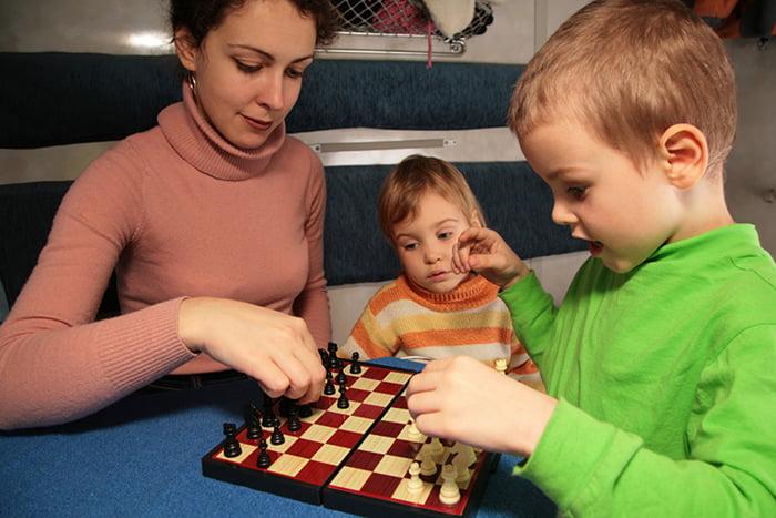 Мама играет с детьми в шахматы в поезде