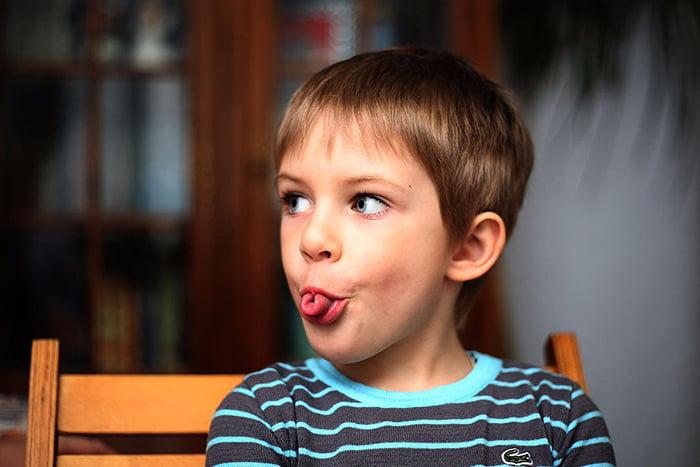 Мальчик свернул язык в трубочку