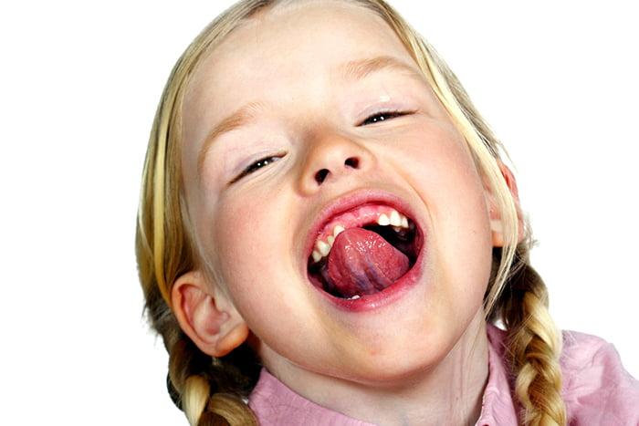 Девочка выполняет гимнастику для языка