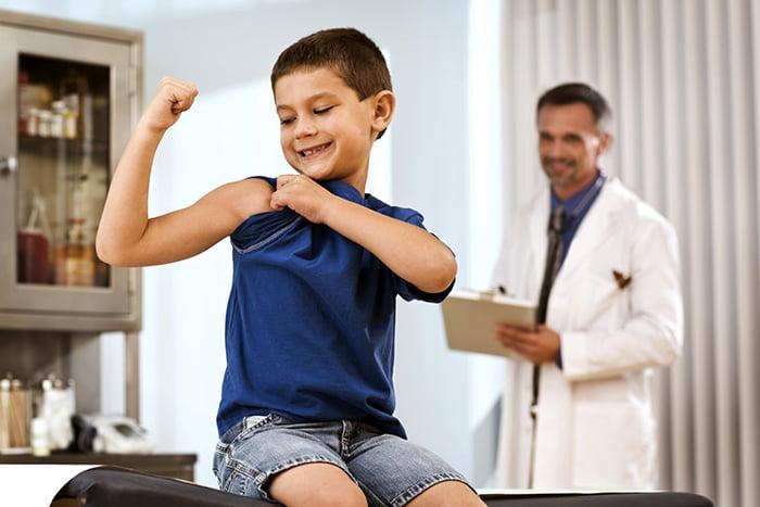 Мальчик демонстрирует бицепс