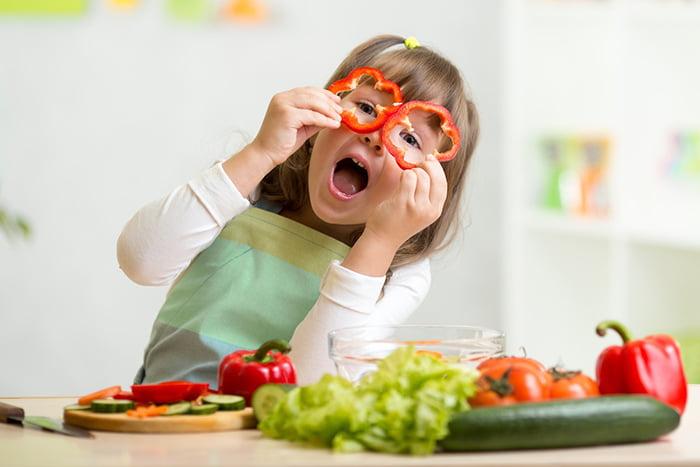 Девочка за столом с овощами