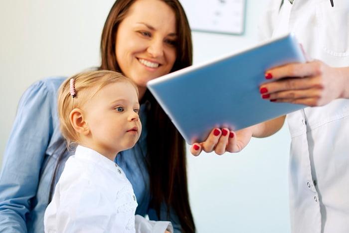 Педиатр показывает центильную таблицу маме и ребенку