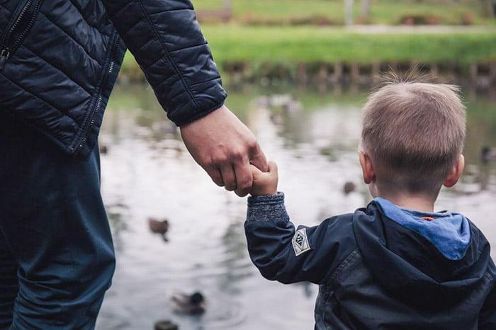 Мальчик держит папу за руку на прогулке у воды