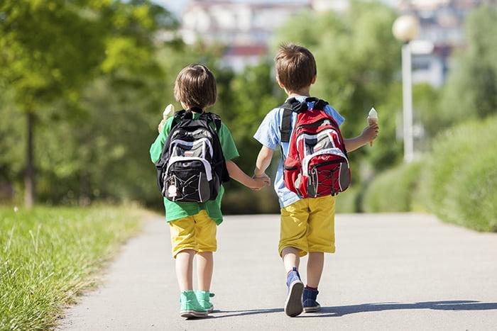 Маленькие дети идут из школы