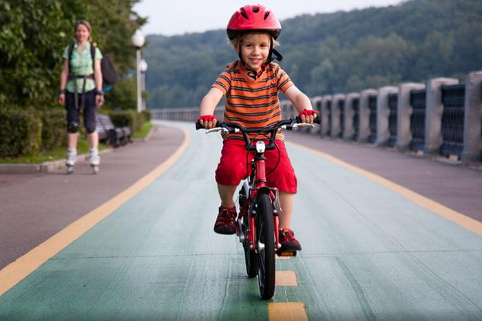 Девочка едет на велосипеде в шлеме