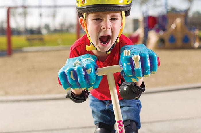 Ребенок едет на самокате в шлеме