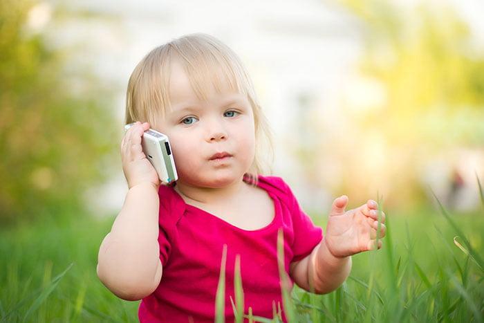 Маленька девочка говорит по мобильному  телефону