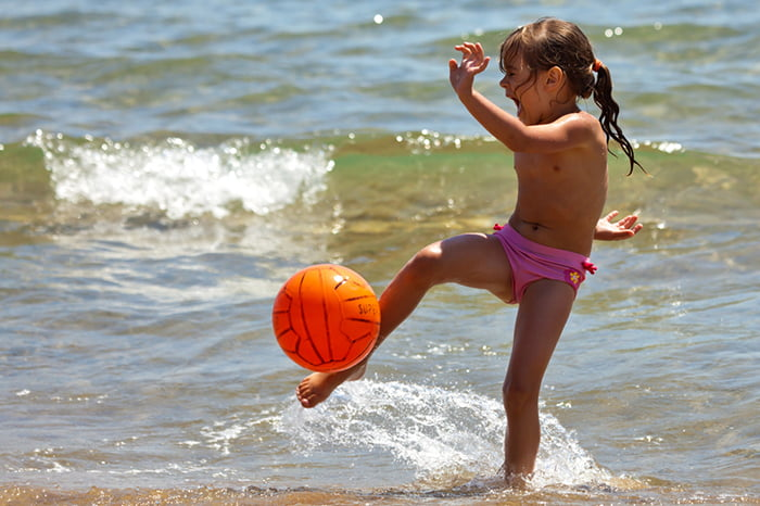 Девочка играет в мяч на берегу моря