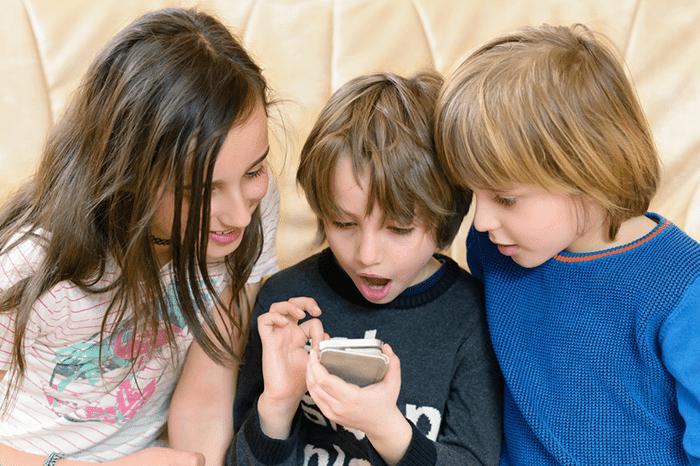 Дети смотрят что-то на смартфоне