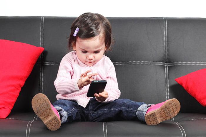 Маленькая девочка пользуется смартфоном