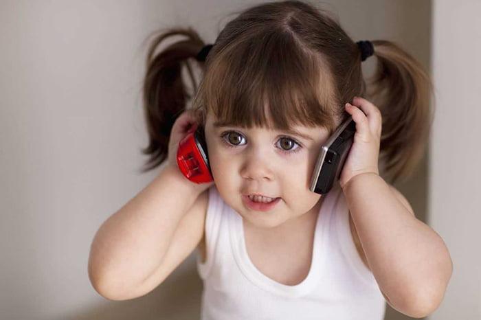 Маленькая девочка с двумя телефонами