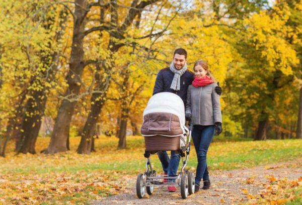 Молодые родители на прогулке осенью